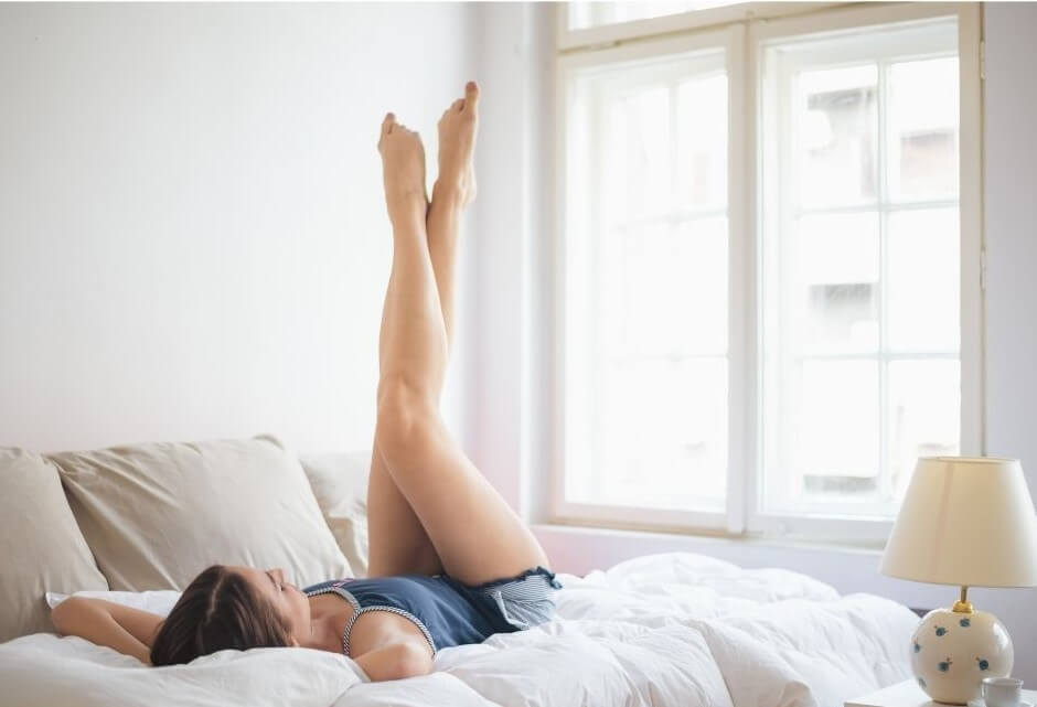 Woman lying on a bed, legs in the air