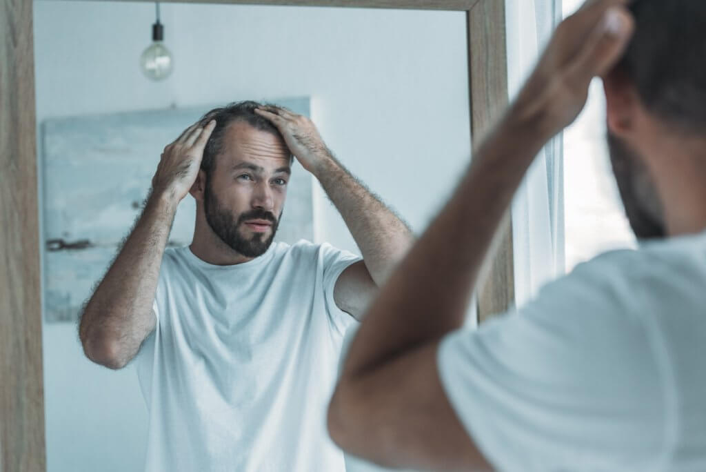 middle aged man looking at mirror hair loss concept