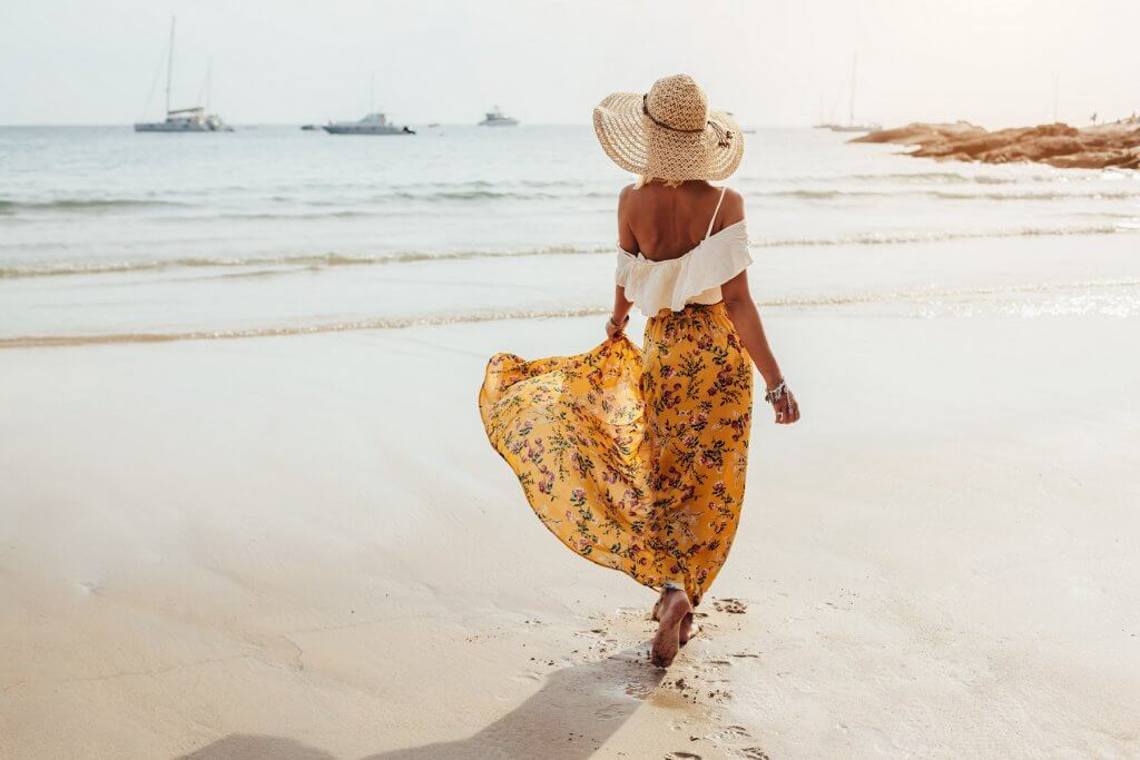 Girl wearing floral maxi skirt walking barefoot on the sea shore